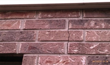 Signs of house needing leveling are evident with cracks on masonry.